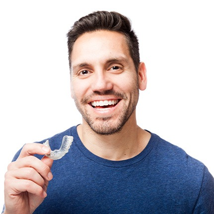 man smiling with oral appliance in hand