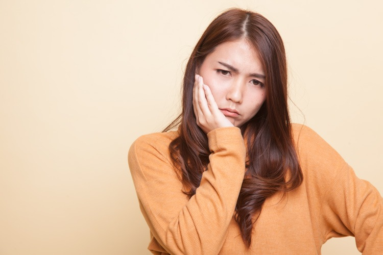 Brunette woman cringes in pain