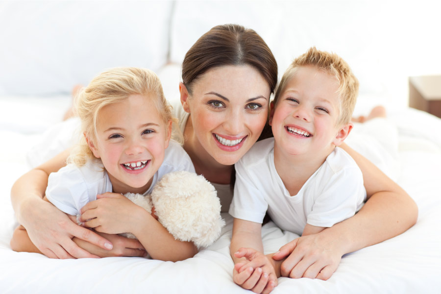 Brunette mother with her two blonde children smile in Fort Smith, AR