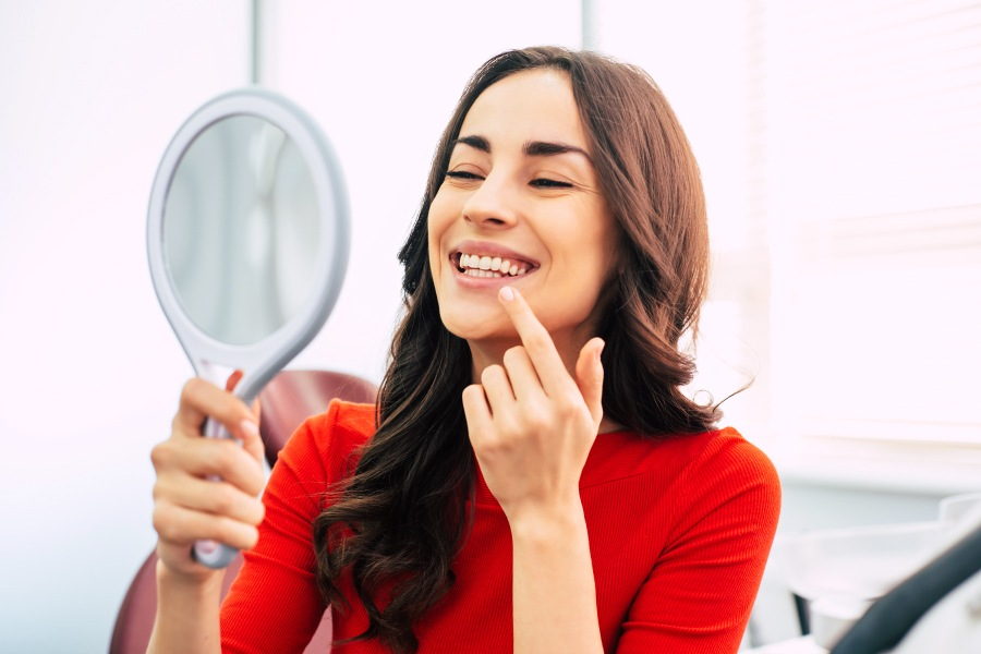Brunette woman in a red shirt smiles while looking at her teeth in a handheld mirror