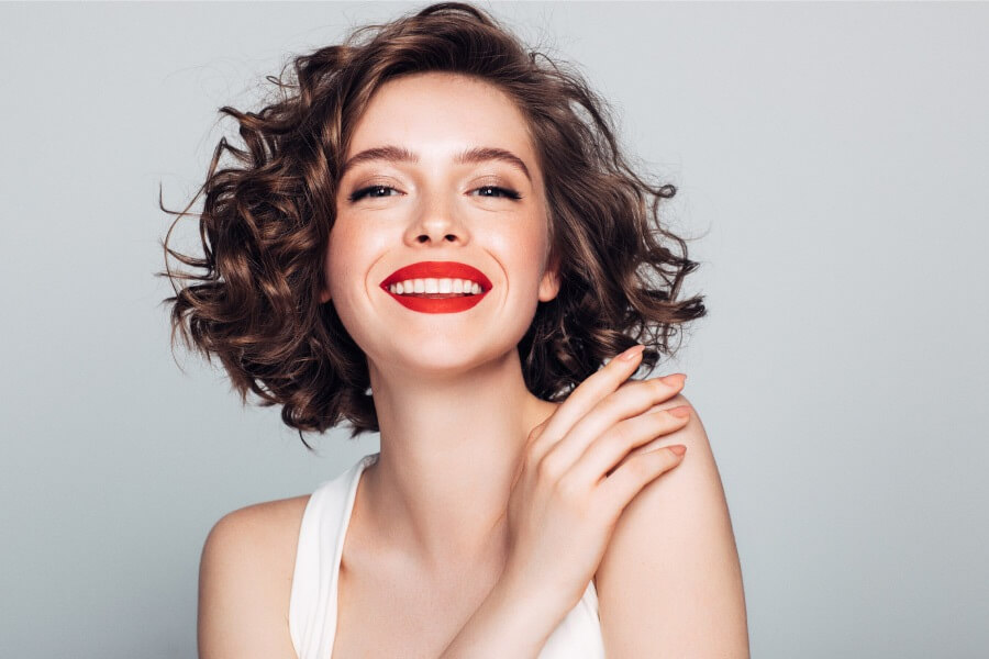 Brunette woman with red lipstick smiles after professional teeth whitening in Fort Smith, AR