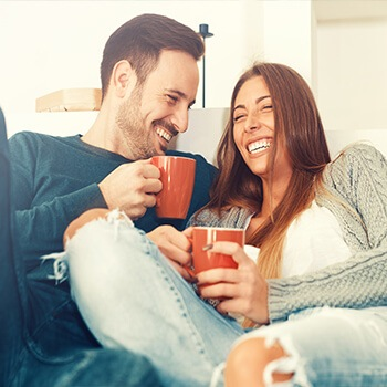 man and woman laughing and having coffee